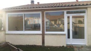Pose d'un ensemble PVC blanc par Solabaie Rochefort, composé d'une porte d'entrée avec fixe latéral et imposte, d'une fenêtre coulissante à 2 vantaux et d'une fenêtre à vantail unique