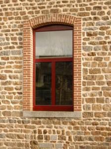 Fenêtre aluminium rouge sur mesure Solabaie installée sur une maison aux murs de pierres et de briques