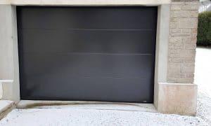 Porte de garage sectionnelle motorisée installée par votre artisan Solabaie Renov' Habitat dans la Manche sur la commune de Terres-et-Marais