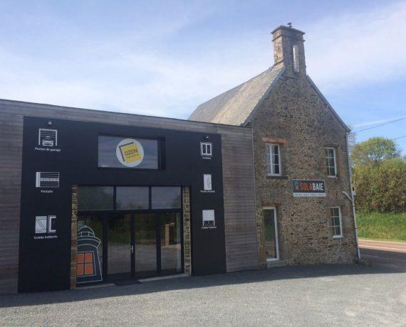 Devanture du magasin de votre installateur Solabaie OZEN Menuiserie, situé à Gratot dans la Manche. Pour vos projets en neuf ou rénovation de fenêtres, portes, volets et portails.