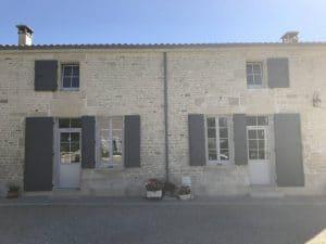Face arrière d'une maison aux menuiseries entièrement rénovées avec des portes d'entrée à impostes et des fenêtres PVC Composium Gris clair à Saint-Pezenne par Solabaie Niort